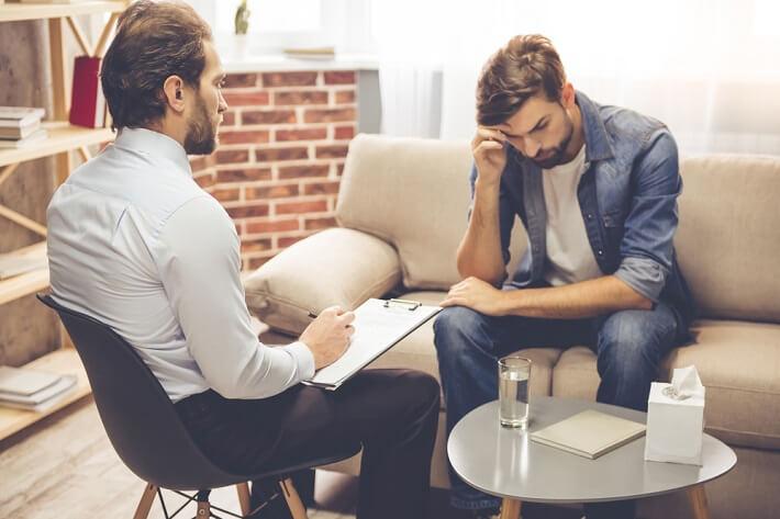 גבר הסובל מדיכאון יושב מול מטפל מומחה בפסיכולוגיה