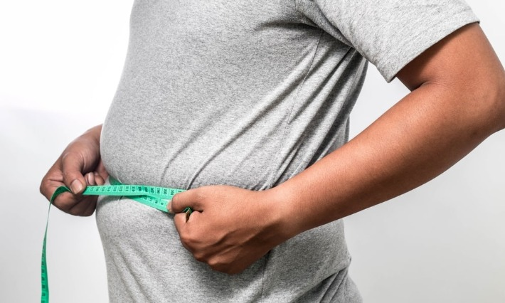 גבר שסובל מעודף משקל מודד את היקף המותניים שלו